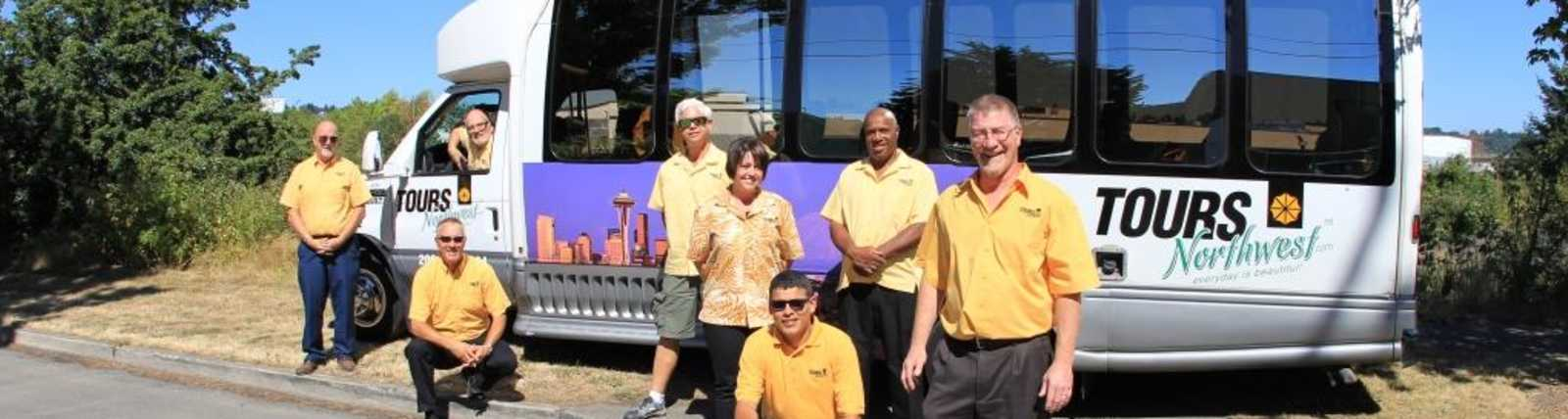 Owner Dan Malmanger stands with members of his staff in front of a tour bus.