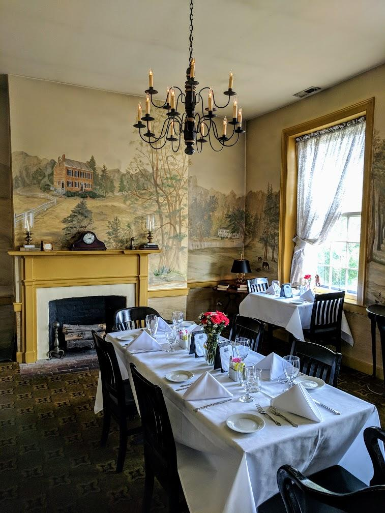 Handpainted murals covering the walls of a dining room in Tousey House Tavern