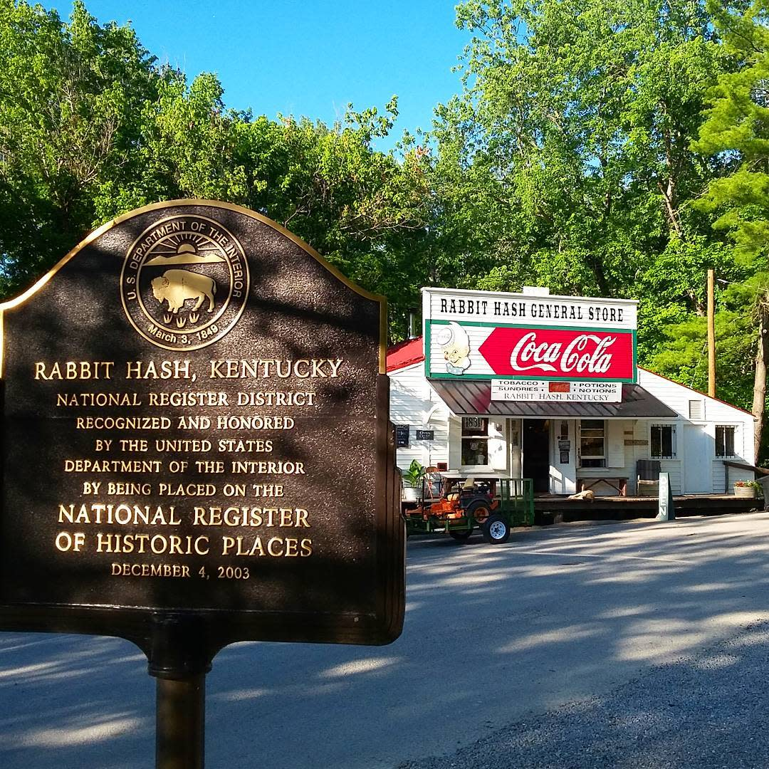 A brown sign noting that Rabbit Hash Kentucky is on the National Historic Register in front of the famous Rabbit Hash General Store