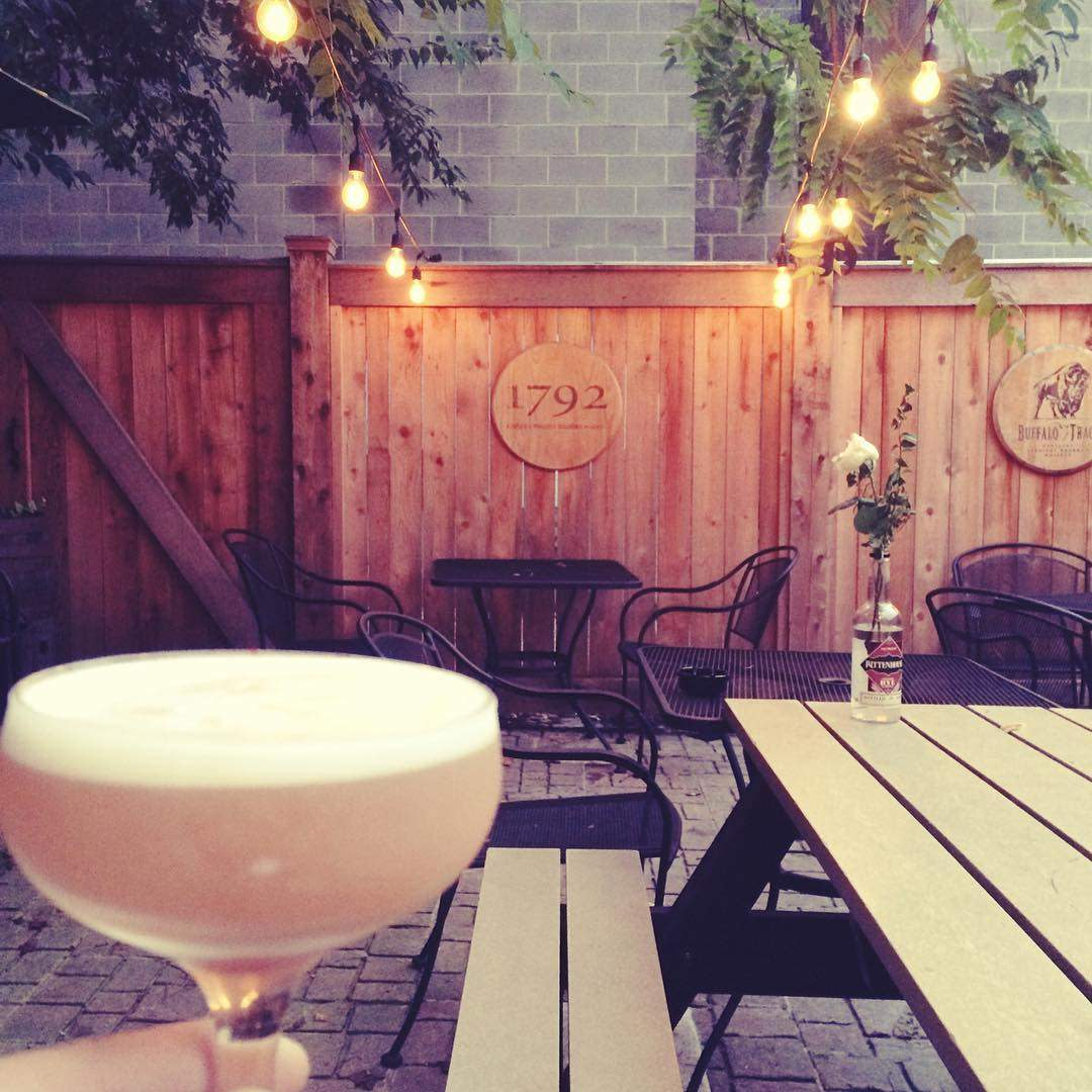 Bourbon cocktail held up with wood and brick patio and string lights in the background