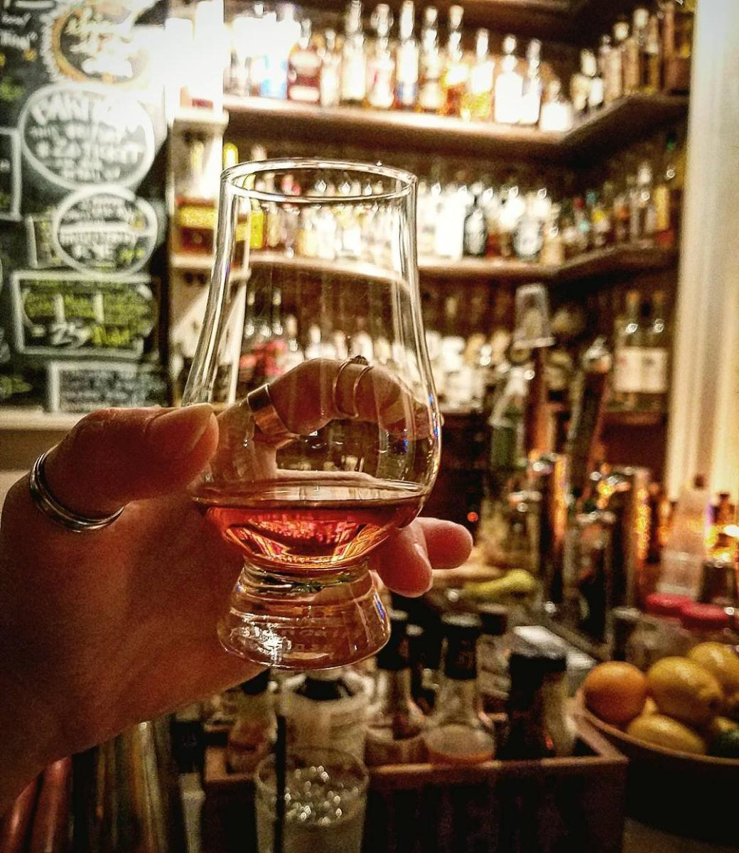 Glencairn glass of bourbon held up with Old Kentucky Bourbon Bar's huge bourbon collection behind it.