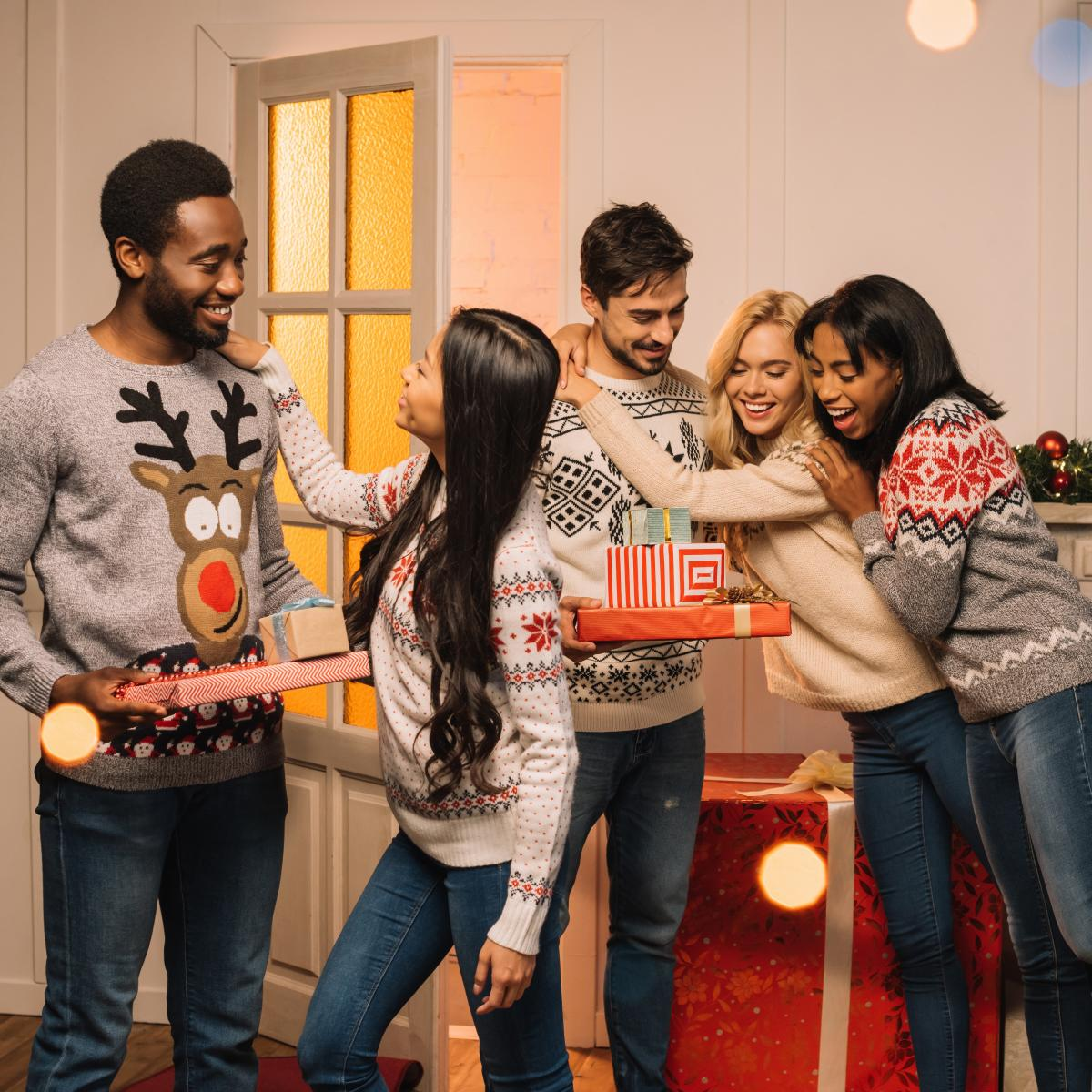 Several friends in tacky holiday sweaters smiling and hugging