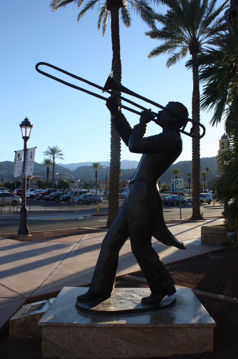 Bronze statue of a man playing a trombone