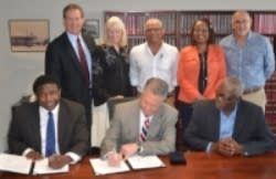 Group photo of Broward County and Costa Rican officials signing document.