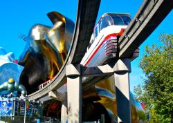 Monorail train leaving Seattle Center and the EMP building