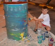 Photo of little boy painting a drum