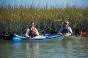 Couple Kayaking near saltmarsh grass at Carolina State Beach Park