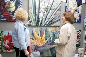 Two women looking at a painting at the Stillwater Arts Festival