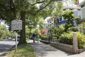 Couple walking past historic district homes