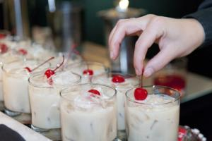 Creamy white cocktail with a cherry on top