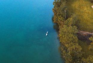 Bird's eye view of a kayaker on the crystal clear waters on Clearwater Lake