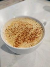 A pumpkin spice latte in a white cup on a table.