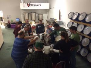 Group of people standing around a table making beer