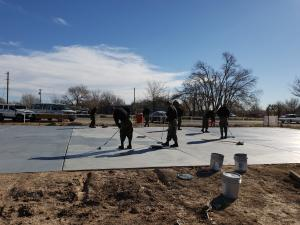 Volunteers paint a basketball court at the park