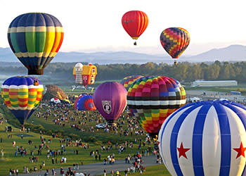 Hot air balloons above the crowds at Adirondack Balloon Festival