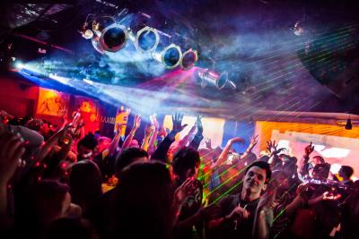 Crowded nightclub dance floor with colorful laser lights & fog over dancers