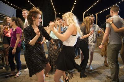 Two young women dancing with crowd of people under fairy lights