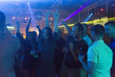 Nightclub with people dancing & drinking under laser lights & disco balls