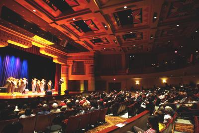 Seated crowd inside the Lincoln Theatre with group of African American singers from the Harlem Gospel Choir on stage