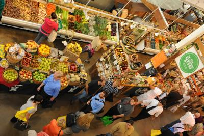 Birds-eye view of people shopping amongst colorful produce in North Market