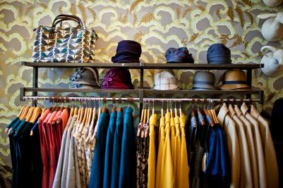 Rack of stylish, colorful clothing and hats from Tigertree in front of patterned wallpaper
