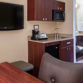 King Suite has Kitchenette area; refrigerator, microwave, sink and TV with a relaxing lounge chair.