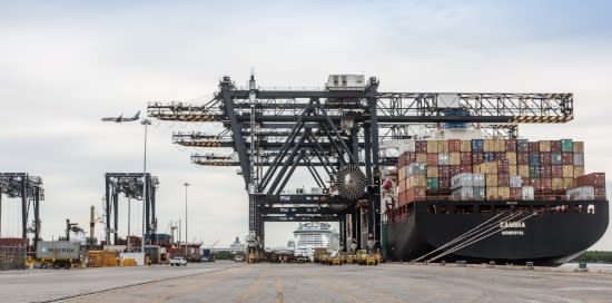 Image of gantry cranes from dock while unloading a containership.
