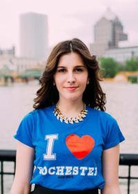 "Rachel stands infront of the Genesee River wearing a ""I Heart Rochester"" T-shirt"