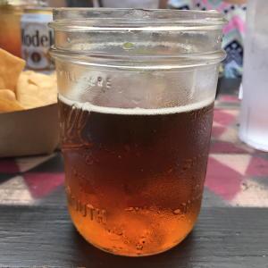 Orange-tinted pumpkin ale in Mason jar