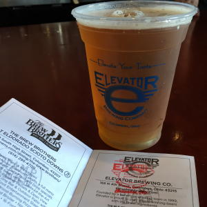 Plastic cup with Elevator Brewing logo filled with beer, sitting on table next to Columbus Ale Trail booklet