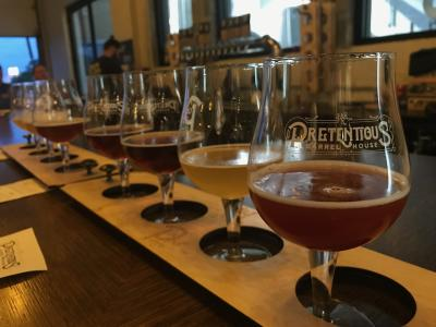 Two flights of four different beers in glasses labelled with Pretentious Brewing's logo