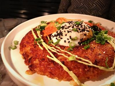 Dish of crispy fried rice topped with soft egg, greens, and a drizzle of sauce from Comune Restaurant