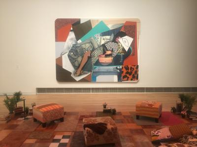 Large collage by Mickalene Thomas picturing a lounging woman, hung in a room with white walls and vibrant, modern furniture