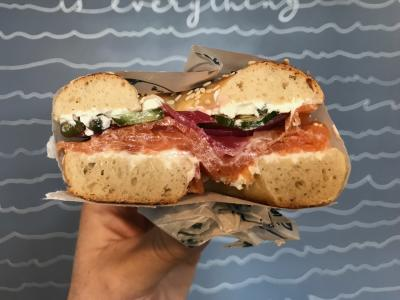 Hand holding half of bagel sandwich topped with meat, greens and spread from Lox Bagel Shop