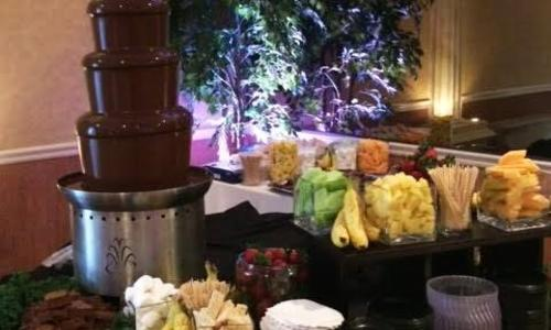 We Do Fondue table with chocolate fountain and cut up fruits