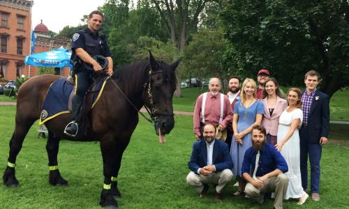 Saratoga Shakespeare Co. cast posing with police officer on horse