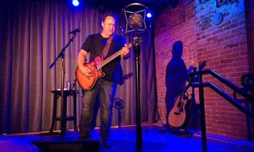 Caffe Lena man and guitar on stage with shadow on wall