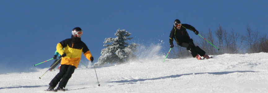 Two downhill skiers on their way down Bristol Mountain.