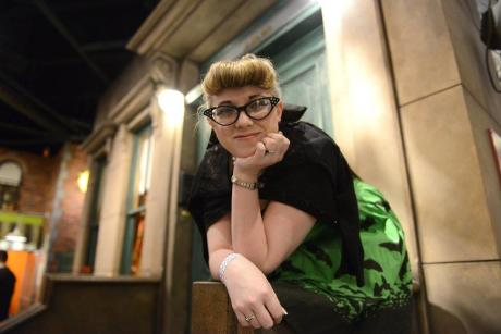 woman stands on the Sesame Street stoop at the Strong Museum