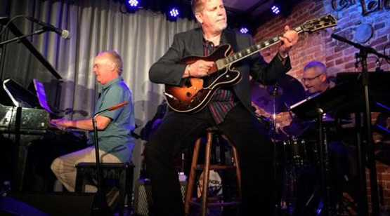 Caffe Lena Man sitting on stool on stage with guitar