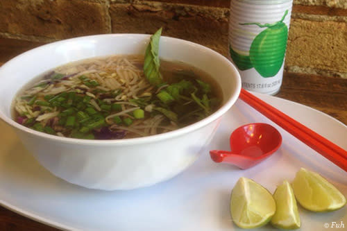 Bowl of pho with lime wedges and chopsticks