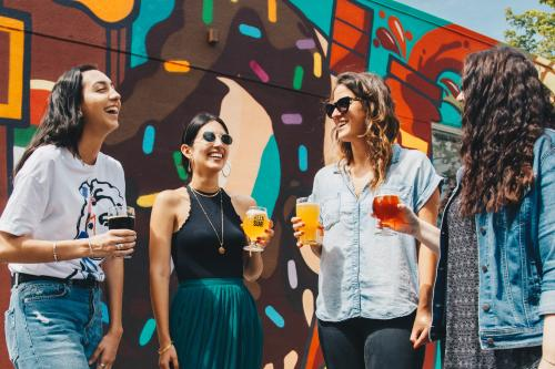 Women enjoying beers in front of a mural at Brews at the Beach Beer Festival in Fort Lauderdale