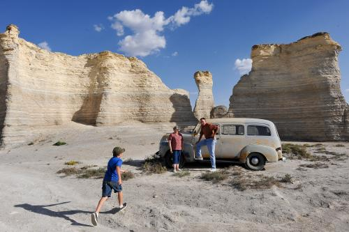 Young boy running to grandparents by antique car at Monument Rocks