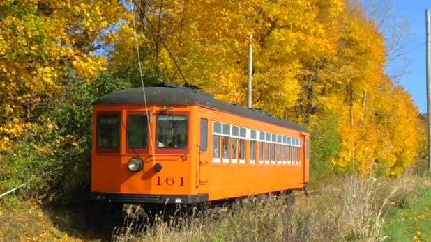Trolley on the tracks along fall foliage