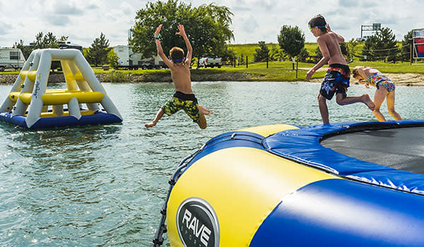 Kids jump off inflatables into lake at the Caboose Lake Campground