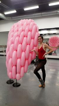 Rochester City Ballet Dancer stands next to a piece of the balloon set created by Airigami Studio