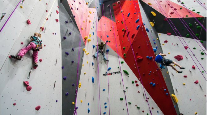A family climbs the wall at Bliss Climbing and Fitness