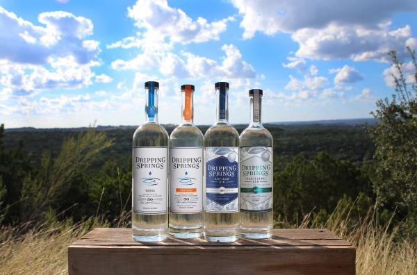 Four bottles of Dripping Springs Vodka and gin in front of hill country landscape