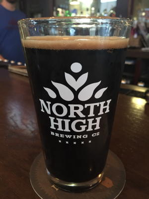 Pint glass with North High Brewing Co. logo full of dark-tinted pumpkin ale