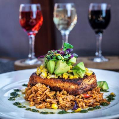 Chipotle Blackened Swordfish  Served on the top of chipotle dirty rice, corn and avocado relish. Behind is the Temecula Wine Flight.